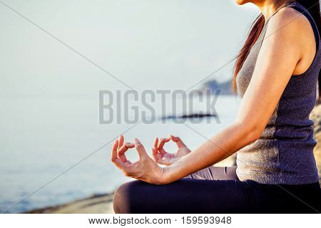 The woman meditating in a yoga pose on the tropical beach. Female meditating overlooking the beautiful sunrise. Healthy mind body and spirit concept.