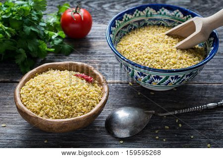 Raw bulgur wheat grains in colorful arabic bowl, fresh parsley, tomato and peppers for cooking. Wooden table background, horizontal composition