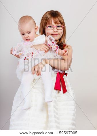 Sisterly love. Two lovely cute little girls. Happy positive childhood of two sisters loving each other. Good emotion.