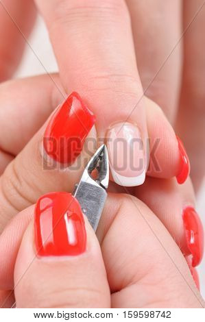 Nail salon, hands beauty treatment, cuticles cutting with nail clippers
