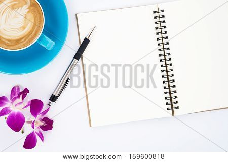Modern White office desk table with empty page leather notebook pen flower and cup of coffee. Top view with copy space.Working desk table concept.