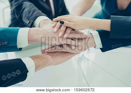 Businesspeople Putting Hands Together On The Table At The Office Meeting