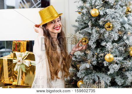 Young woman in sweater and golden hat decorating Christmas tree at home. Preparation to New Year holiday