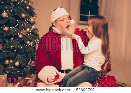 Smart Little Girl Sitting On The Lap Of Old Santa And  Pulling His Beard,  Check He Real Or Fake In