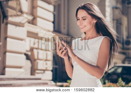 Happy brunette woman typing sms on smartphone in city poster