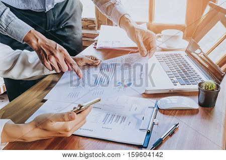 Business team analyzing income charts and graphs with modern laptop computer and using smart phone. Top view close up