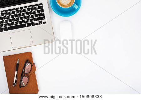 Modern White office desk table with laptopleather notebook pen eyeglasses mouse and cup of coffee.Top view with copy space.Working desk table concept.