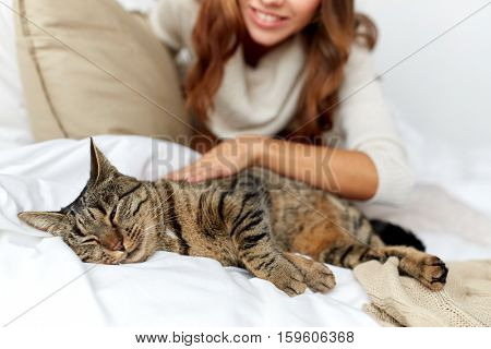 pets, comfort, rest and people concept - happy young woman with cat lying in bed at home