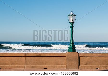 Lamppost on the Mission Beach boardwalk in San Diego, California with ocean waves in the background.