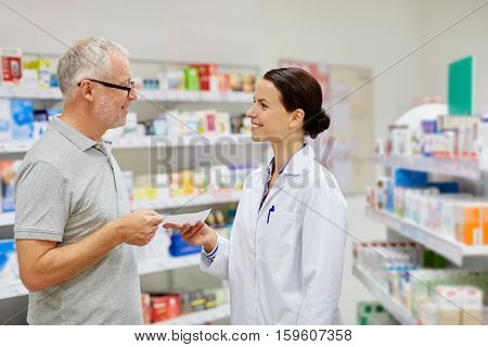 medicine, pharmaceutics, health care and people concept - happy senior man giving prescription to pharmacist at drugstore