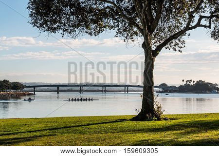SAN DIEGO, CALIFORNIA - DECEMBER 2, 2016: A rowing team practicing on Mission Bay in San Diego, California as seen from Ventura Cove Park.