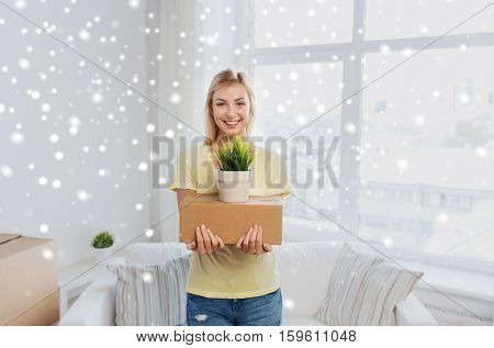 moving, delivery, accommodation and people concept - smiling young woman with cardboard box and plant at home over snow