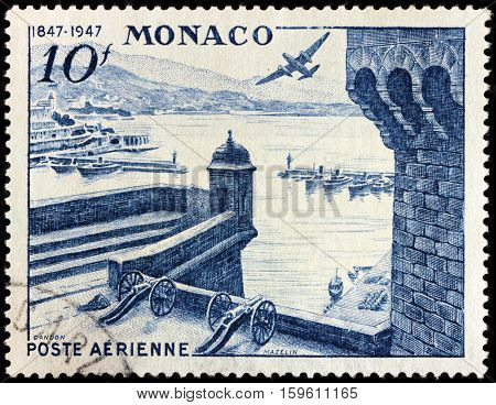 LUGA RUSSIA - NOVEMBER 29 2016: A stamp printed by MONACO shows beautiful view of Monte Carlo with Port Hercules fortress and airplane Douglas DB 7 Boston over Monaco circa 1947