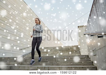 fitness, sport, people and healthy lifestyle concept - happy sporty woman running downstairs in city