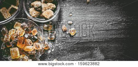 Brown Cane Sugar. On Black Rustic Background.