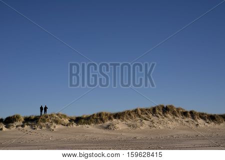 Two people on dunes at the Danish North Sea coast. The beach of Skallingen Esbjerg.