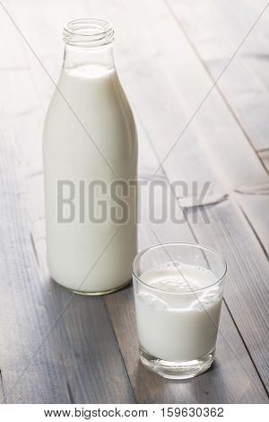 glass cup and bottle full of milk on wooden table