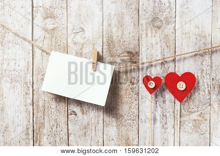 Valentine's day or love concept. Piece of paper with wooden clamp on rope with hearts horizontal