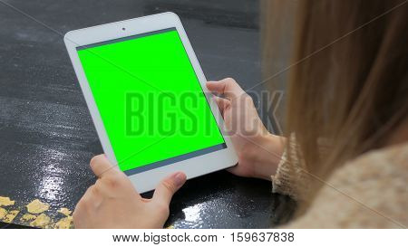 Woman looking at vertical tablet computer with green screen. Close up shot of woman's hands with pad
