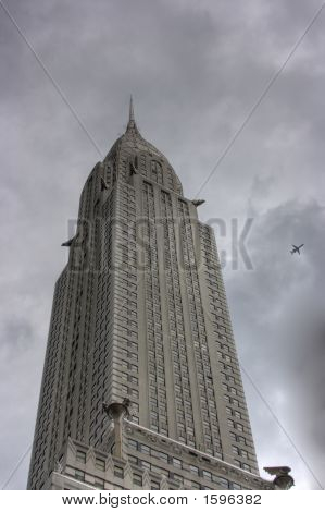 Skyscraper With Dark Clouds And An Airplane Flying Overhead