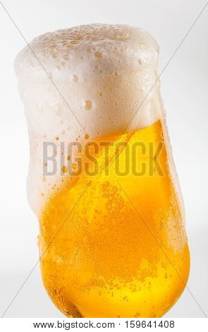 Overflowing beer with foam in a tulip glass