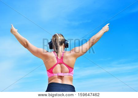 Success fitness winning woman concept with earphones. female athlete runner cheering arms raised up for achievement in weight loss or life goal.