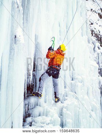 Ice climbing the North Caucasus, man climbing frozen waterfall.
