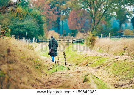 Woman With Shoulder Bag Walking In Field With Autumn Trees.
