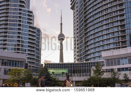 TORONTO,CANADA-AUGUST 2,2015:Urban life near the CN tower in Toronto during a sunset from one of the central street of the city