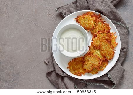 Latkes and sour cream in a plate traditional hannukkah dish view from above space for a text