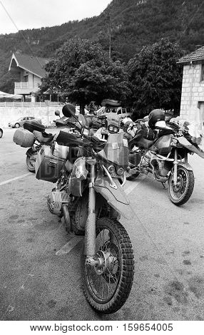 Black and white photography of group motorbikes parked together on outdoors background. BW shot with high grain ISO400 film.