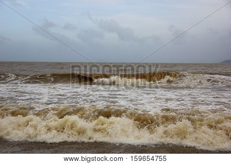 Turbulent seas of Vietnam, a strong wave twist yellow sand, and it turns out the sea sand color, the sky with clouds