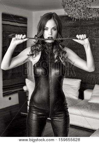 Sexy dominatrix in latex catsuit holding whip black and white