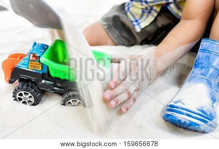 Child playing with toy car in a sand playground.