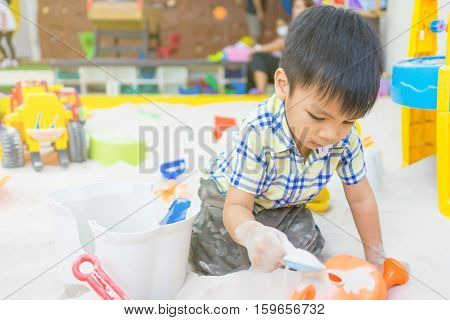 Boy is playing with sandbox toys in educational playground. This fine sand are specially clean and made for children playground.