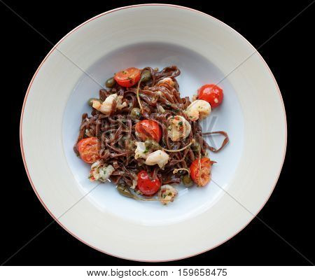 Rye pasta with capers and prawns isolated on black background