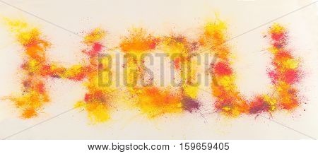 Word Holi painted by splash of multicolor paint on white background
