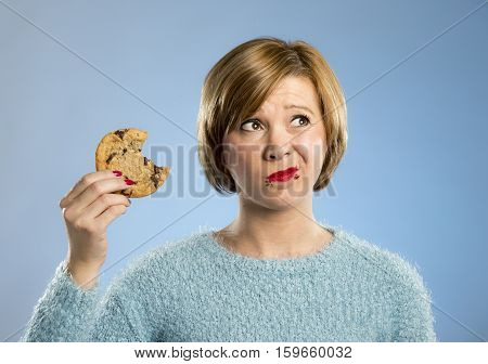 young blond cute beautiful caucasian woman with chocolate stain in her mouth eating big delicious cookie looking with temptation thinking if ignoring diet vs sweet junk food isolated background