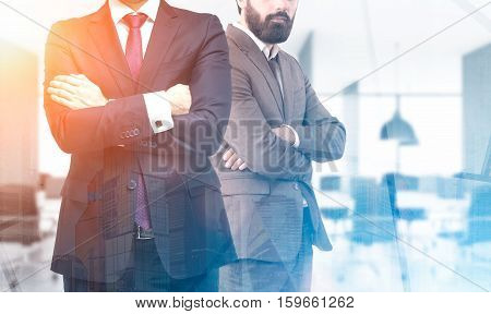 Two business partners are standing together in an office. Their arms are crossed. Cityscape. Toned image. Mock up. Double exposure