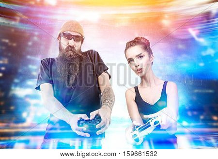 A geeky girl in a tank top and a brutal man with a long beard are playing two video game consoles in virtual reality. Toned image