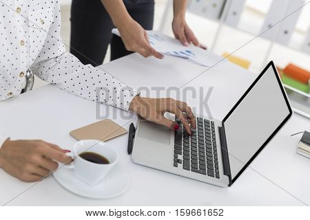 Close up of women's hands. One is typing and holding a white cup of coffee. The second is handing her graphs. Mock up