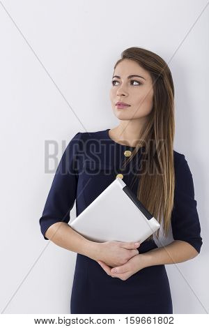 Portrait of a woman in a dark dress holding her tablet and looking sideways while standing near a white wall.