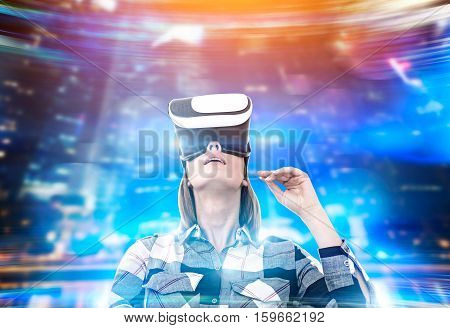 Portrait of a woman in a flannel shirt wearing virtual reality glasses and standing in a holographic place. Toned image.