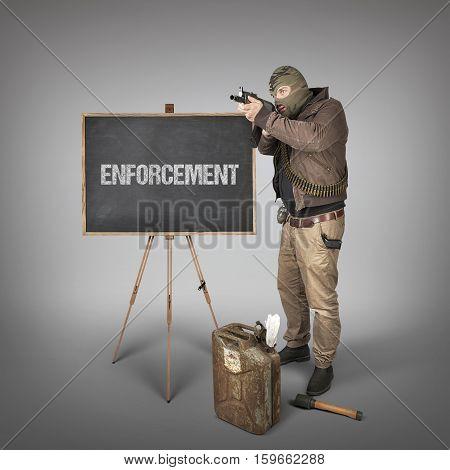 Enforcement text on blackboard with terrorist holding machine gun
