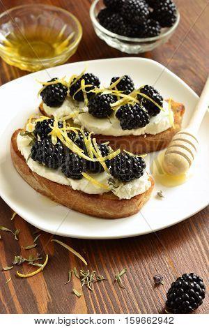 Crostini with goat cheese blackberries lemon zest and honey, vertical