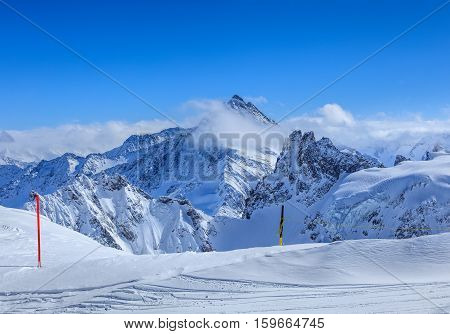 View from Mt. Titlis in the Swiss Alps in winter. Mount Titlis is a mountain located on the border between Swiss Cantons of Obwalden and Bern.