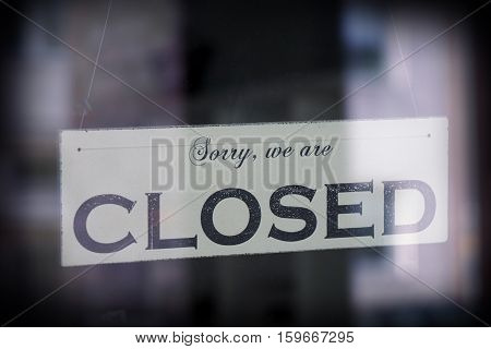 sign saying sorry we are closed, behind glass with reflection, selective focus, vintage filter