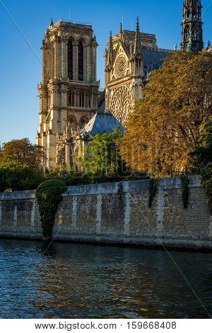 Notre Dame de Paris cathedral at sunset with the Seine River on Ile de La Cite. Autumn evening in Paris France