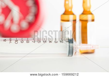 Injection syringe and brown ampule on red clock background