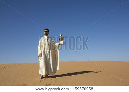 Dubai, UAE, November 2016: Tunisian man with a seaker falcon in a desert at sunrise